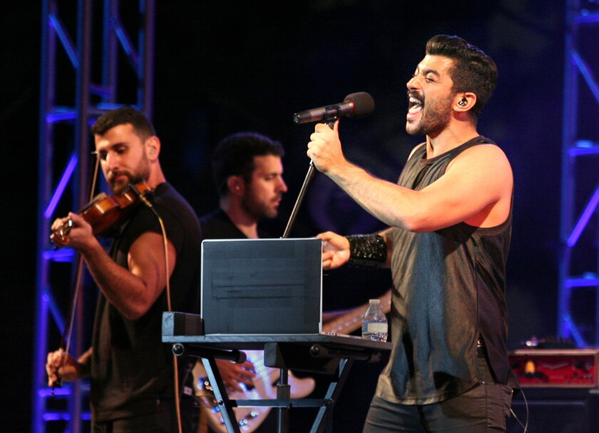 The band Mashrou' Leila, a Lebanese five-piece alternative rock group, performed downtown as part of Grand Performances on Friday night. At right is lead singer Hamed Sinno.