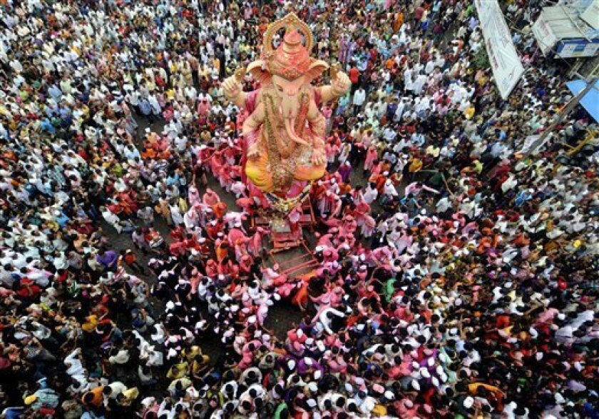 Devotees sing and dance as they carry an idol of Hindu elephant-headed God Ganesh in a procession for immersing it in the Arabian Sea at the end of the ten day festival in Mumbai, India, Sunday, Sept. 11, 2011.(AP Photo/Rajanish Kakade)