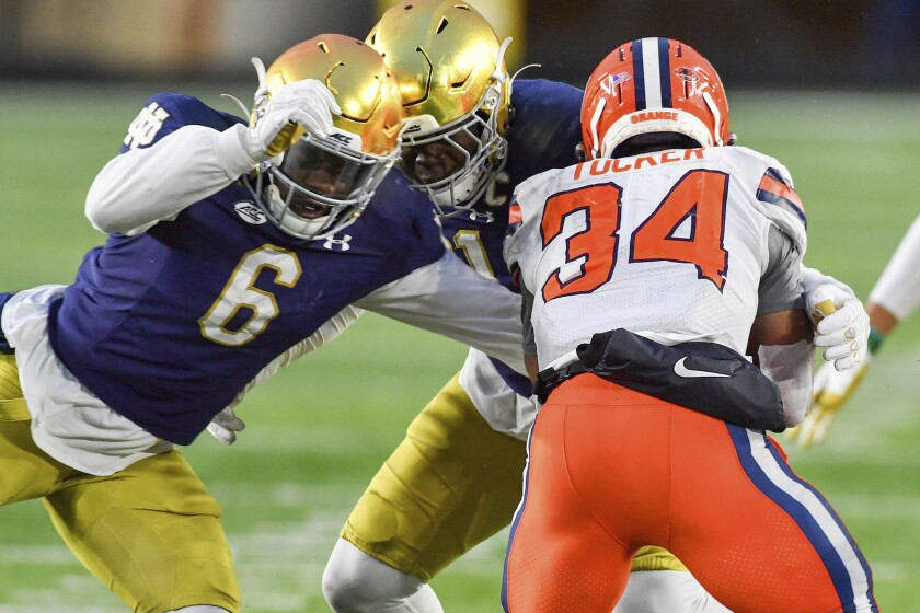 Syracuse running back Sean Tucker (34) is tackled by Notre Dame linebacker Jeremiah Owusu-Koramoah (6) during the third quarter of an NCAA college football game Saturday, Dec. 5, 2020, in South Bend, Ind. (Matt Cashore/Pool Photo via AP)