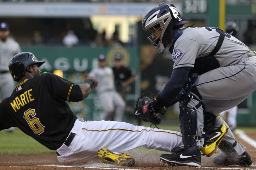 Padres catcher John Baker tags out Pittsburgh's Starling Marte trying to score on a ground ball in the first inning.