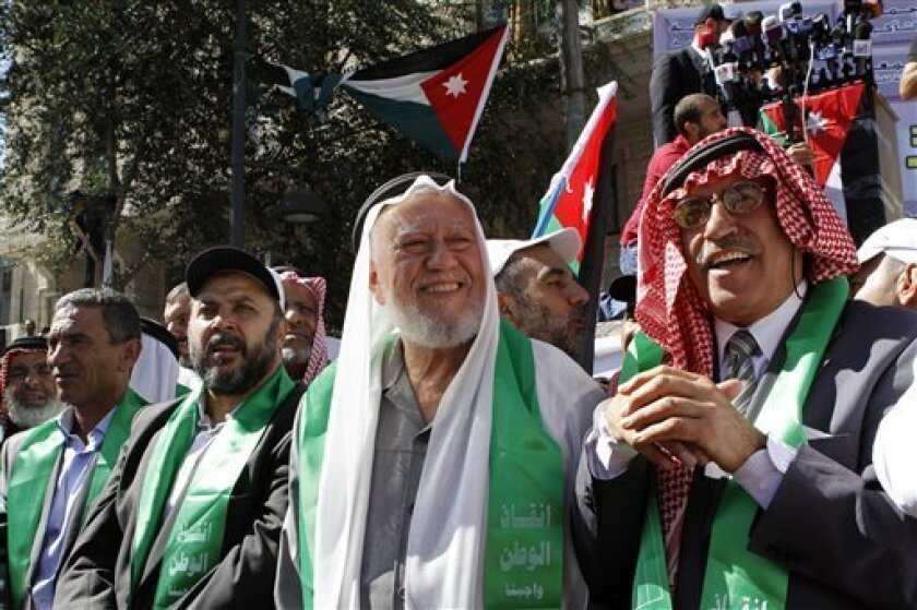 Secretary General of the Jordanian Islamic Action Front Hamza Mansour, center, is among thousands of Islamic Action Front supporters demanding constitutional reforms during an opposition rally described as the biggest in the kingdom since the Arab Spring uprisings started in late 2010, in Amman, Jordan, Friday, Oct. 5, 2012. (AP Photo/ Raad Adayleh)