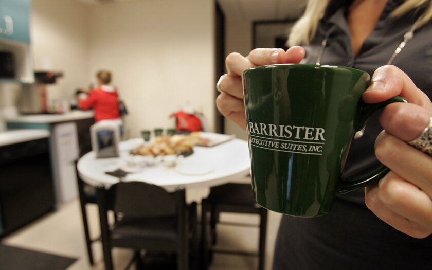 Small business executives, moving out of their home offices, sometimes select executive suite offices such as Barrister's in Mission Valley. Every Friday tenants gather and network.  Jodie Rowe holds up a Barrister executive suites mug.
