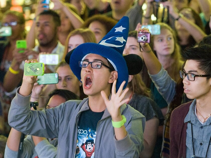 FILE - In this Aug. 2013 file photo, fans attend an event at Disneyland in Anaheim, Calif. Seven Californians and two people in Utah have confirmed cases of measles likely contracted on trips last month to Disney theme parks in California, state officials said Wednesday, Jan. 7, 2015. (AP Photo/The