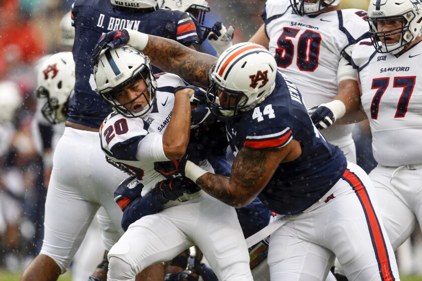 FILE - In this Saturday, Nov. 23, 2019 file photo, Samford running back Jay Stanton (20) is tackled by Auburn defensive tackle DaQuan Newkirk (44) during the first half of an NCAA college football game in Auburn, Ala. Florida is rebuilding its defensive line with help from the transfer portal. The Gators officially welcomed former Auburn defensive tackle Daquan Newkirk to the program Thursday, Jan. 14, 2021 a little more than a week after landing Penn State defensive tackle Antonio Shelton. (AP Photo/Butch Dill, File)