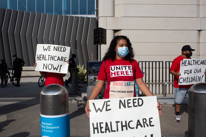 """People at Los Angeles International Airport hold signs that say """"We need healthcare now!"""" and """"Healthcare for our children!"""""""