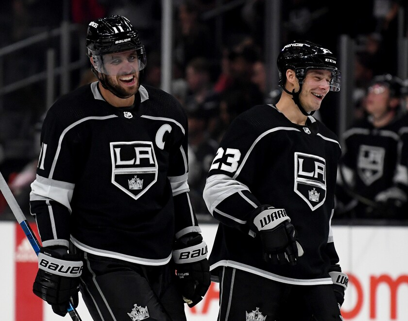 Kings forward Anze Kopitar celebrates his empty net goal with teammate Dustin Brown during a preseason win over the Ducks on Sept. 23.