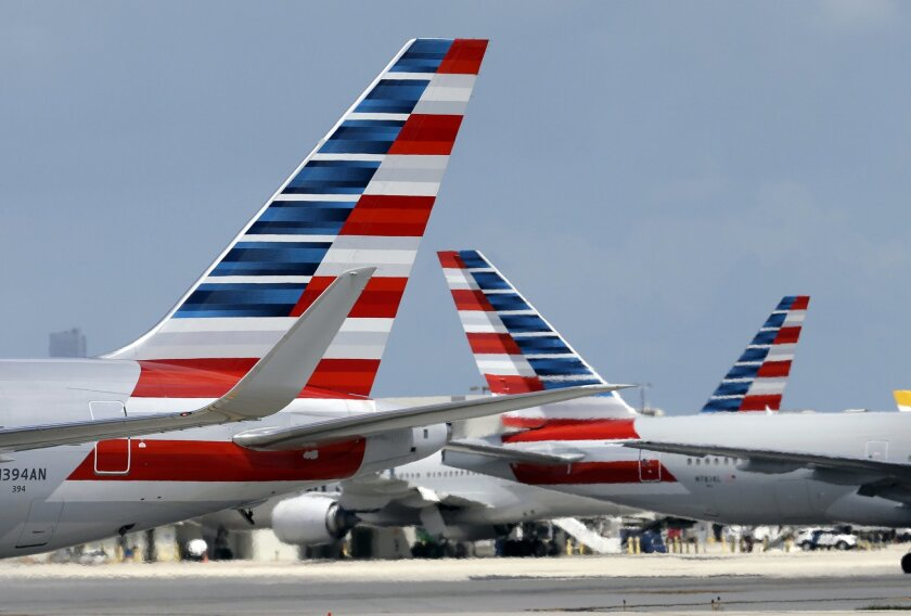 In this May 27, 2015, photo, American Airlines aircraft taxi at Miami International Airport in Miami. American Airlines reports quarterly financial results on Friday, July 24, 2015. (AP Photo/Lynne Sladky)