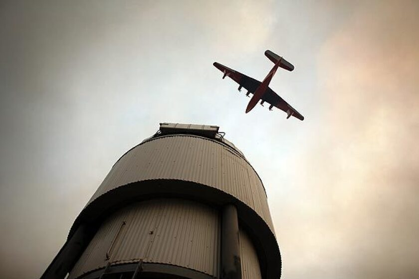 A Martin Mars Super Scooper flies over Mt. Wilson Observatory and radio towers Tuesday.
