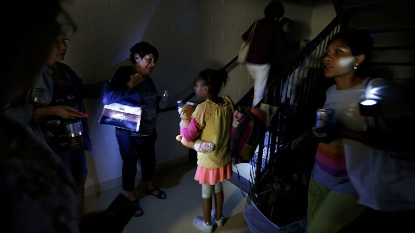 With the lights out at the Hampton Inn and Suites in Estero, Fla., the evacuees help one another make their way to the stairway with flashlights.