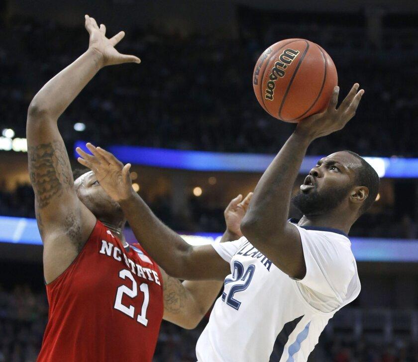 Villanova's JayVaughn Pinkston (22) shoots over North Carolina State's Beejay Anya (21) during the first half of an NCAA tournament third-round college basketball game, Saturday, March 21, 2015, in Pittsburgh. (AP Photo/Gene J. Puskar)