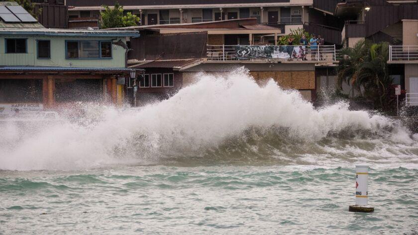 Visitors watch waves generated by Hurricane Lane crash at Kailua-Kona.