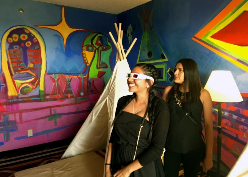 This May 5, 2016 photo Kalene Thompson, left, views an installation art piece by contemporary Native American artist Ishkoten Dougi through 3D glasses at the Nativo Lodge in Albuquerque, N.M. Nativo Lodge has transform 12 guest rooms in recent years into spaces that owners say can be considered art