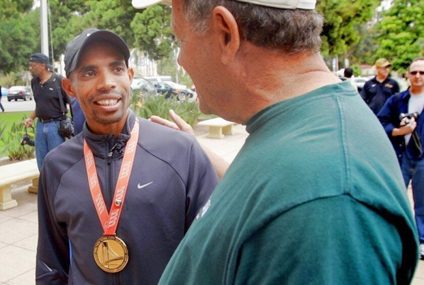 New York City Marathon winner Meb Keflezighi received a warm welcome at the San Diego Hall of Champions Friday. Here he is congratulated by Dick Lord, his coach when Keflezighi attended Roosevelt Junior High.