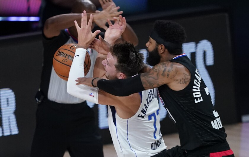 Dallas Mavericks star Luka Doncic is fouled by Clippers forward Marcus Morris Sr.