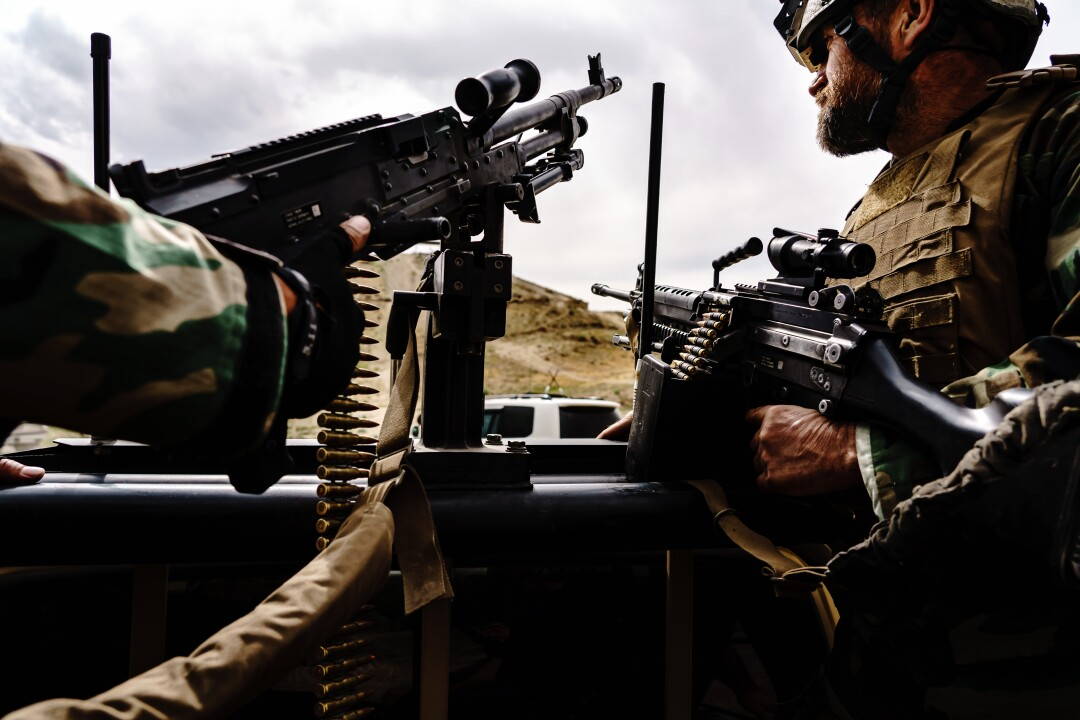 Soldiers hold automatic weapons.