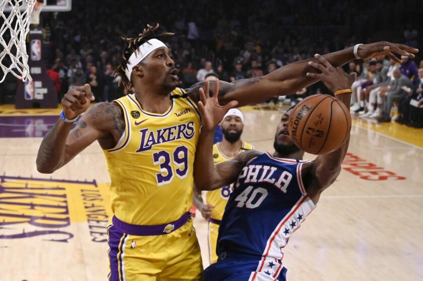 Los Angeles Lakers center Dwight Howard, left, blocks the shot of Philadelphia 76ers forward Glenn Robinson III.