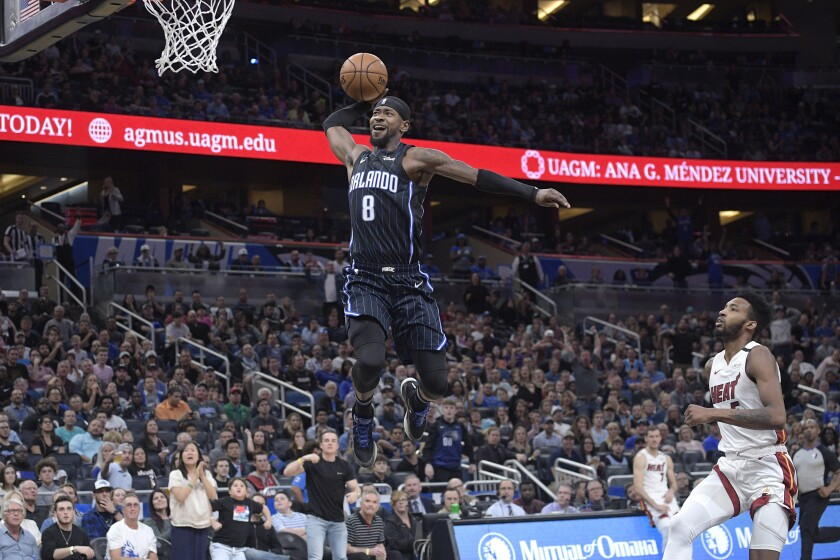 Orlando Magic guard Terrence Ross (8) goes up for a breakaway dunk in front of Miami Heat forward Derrick Jones Jr., right, during the second half of an NBA basketball game Friday, Jan. 3, 2020, in Orlando, Fla. (AP Photo/Phelan M. Ebenhack)