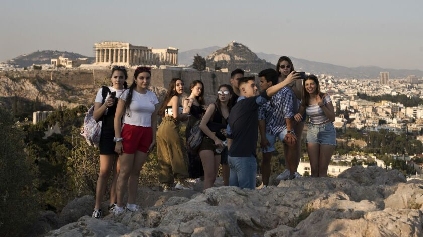 Young tourists pause for photos in Athens.