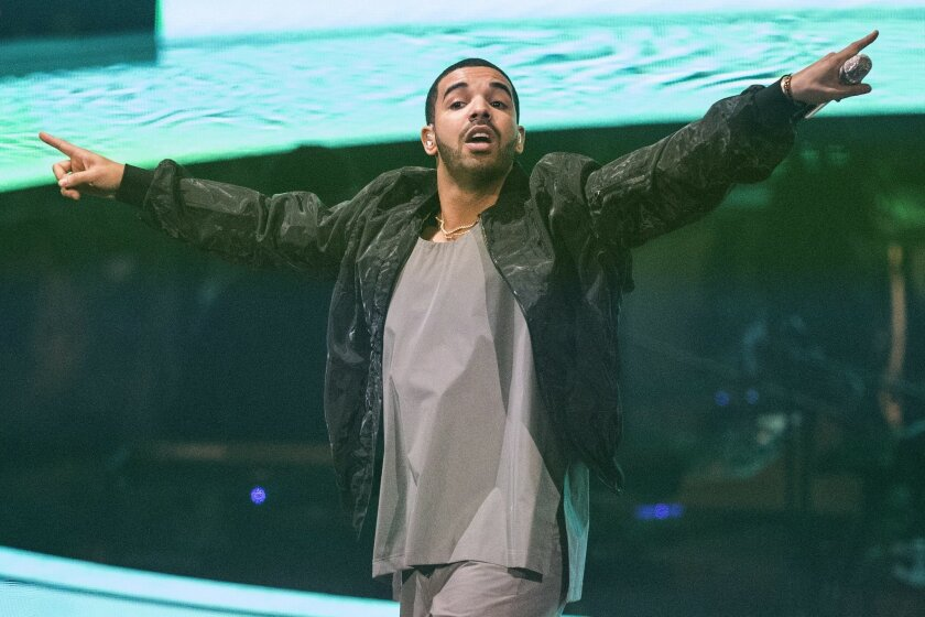 """FILE - In this Oct. 24, 2013 file photo, Drake performs during his """"Would You Like A Tour"""" show in Toronto. The Toronto-based rapper, singer and actor will host the July 16, 2014, ESPYs sports awards show on ESPN in Los Angeles. The Grammy-winning rapper gave $75,000 for a recording studio at Strawberry Mansion High School in Philadelphia. (AP Photo/The Canadian Press, Chris Young, file)"""