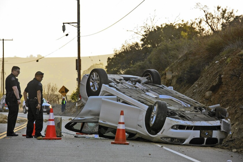 Caltrans workers and Brea police inspect a BMW that overturned during a rock slide in Carbon Canyon after the 5.1 La Habra earthquake last year.