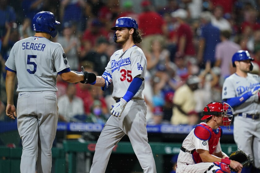 Los Angeles Dodgers' Cody Bellinger, center, celebrates with Corey Seager, left, after hitting a two-run home run of Philadelphia Phillies pitcher Kyle Gibson during the fourth inning of a baseball game, Wednesday, Aug. 11, 2021, in Philadelphia. (AP Photo/Matt Slocum)