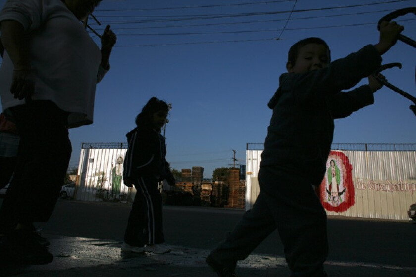 Children walk down a stretch of East 29th Street in South Los Angeles. Los Angeles officials are in the final stages of negotiating a complex settlement that would relocate a metal finishing plant that has been the bane of a poor neighborhood, replacing a stretch of blocks that are gritty even by the standards of South L.A. with a large affordable-housing project.. More photos >>>