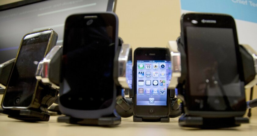 FILE - This Wednesday, Feb. 19, 2014 file photo shows a display of cell phones during a Federal Trade Commission (FTC) mobile tracking demo in Washington. On Friday, May 27, 2016, National Institutes of Health expert reviewers said they are finding flaws in the agency's new study that connects heav