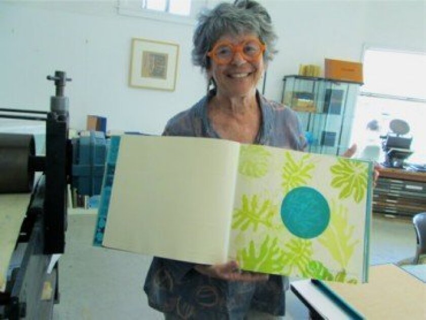 At Bay Park Press, Sibyl Rubottom shows off one of her illustrations from 'The Second Quarter,' a book of poems by her son, Otis Rubottom, printed especially for the opening of her show at La Jolla's Athenaeum Music & Arts Library.