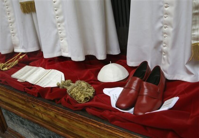 Papal shoes and a white skull cap are seen beneath three sets of papal outfits - small, medium and large sizes - which will be sent to the Vatican for the new pope, are displayed in the Gammarelli tailor shop window, in Rome, Monday, March 4, 2013. For over a half century the Gammarelli family has