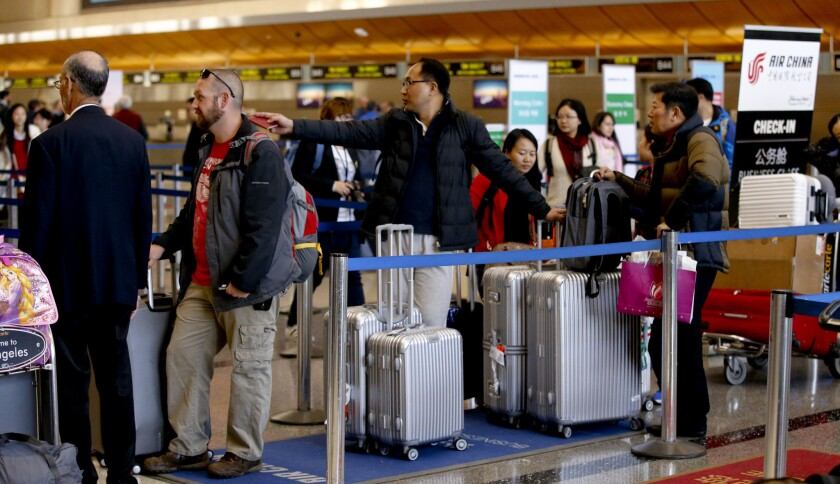 Travelers line up at the check-in counter for Air China inside the Bradley Terminal at Los Angeles International Airport. The number of flight searches by international travelers to the U.S. dropped after Trump's travel ban was adopted.