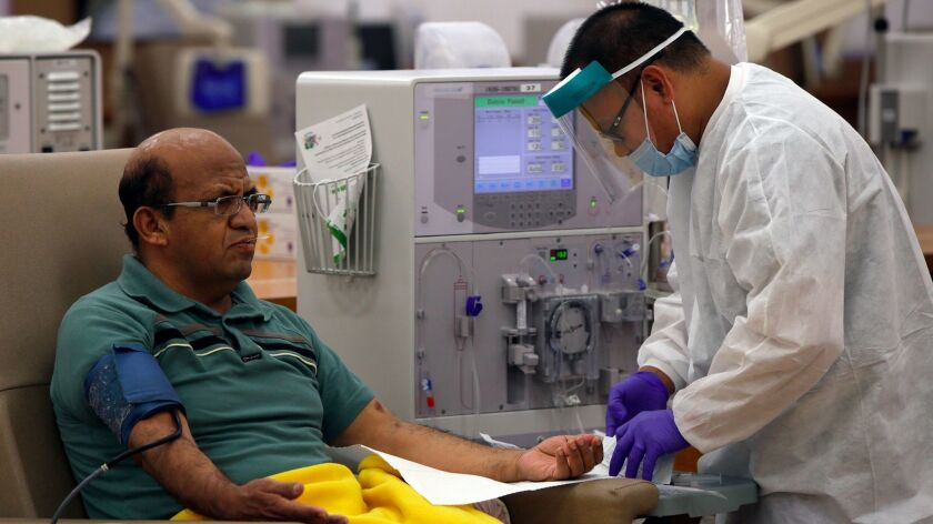 Giraldo Garcia waits for dialysis as a patient care technician preps him at a DaVita Dialysis Center in Inglewood in 2014.
