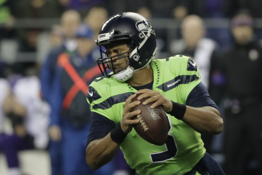 Seattle Seahawks quarterback Russell Wilson drops to pass against the Minnesota Vikings during the first half on Monday in Seattle.