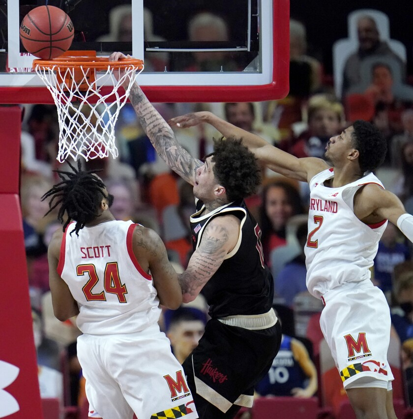 Nebraska guard Teddy Allen, center, goes up for a shot against Maryland forward Donta Scott, left, and guard Aaron Wiggins during the second half of an NCAA college basketball game, Tuesday, Feb. 16, 2021, in College Park, Md. Maryland won 64-50. (AP Photo/Julio Cortez)