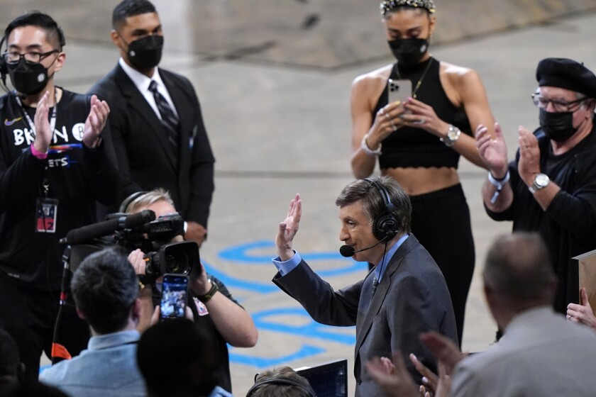 Broadcaster Marv Albert, who is retiring, acknowledges the crowd's applause during the first half of Game 5 of a second-round NBA basketball playoff series between the Brooklyn Nets and the Milwaukee Bucks, Tuesday, June 15, 2021, in New York. (AP Photo/Kathy Willens)