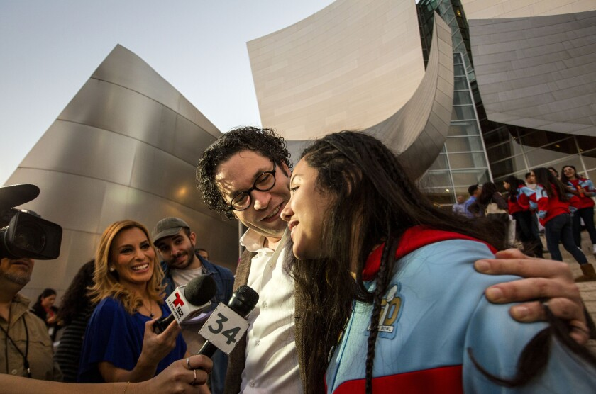 Los Angeles Philharmonic's Gustavo Dudamel and YOLA cellist Karla Melgar are interviewed by TV reporters outside Disney Hall in downtown L.A.