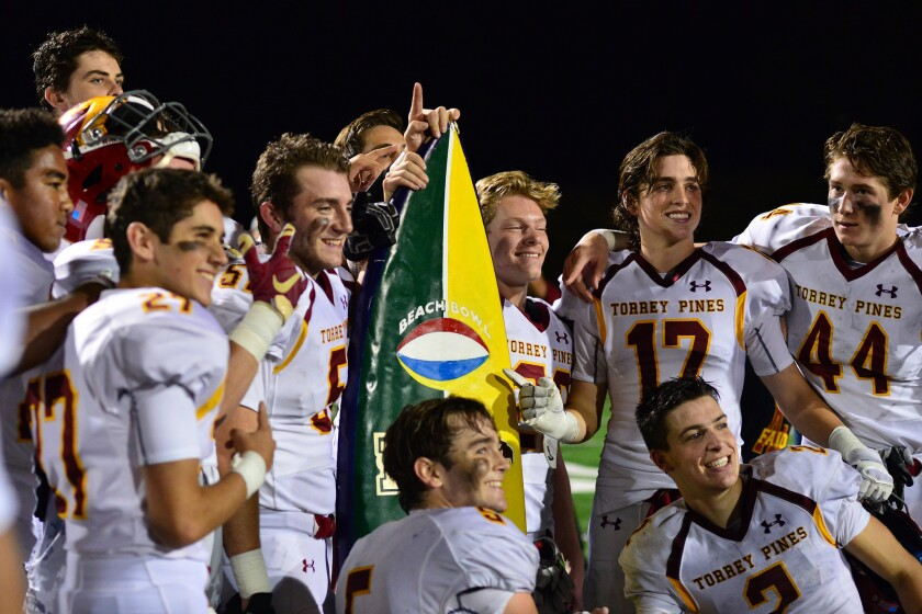 The Torrey Pines High School varsity football team celebrates its recent Beach Bowl win over La Costa Canyon High School.