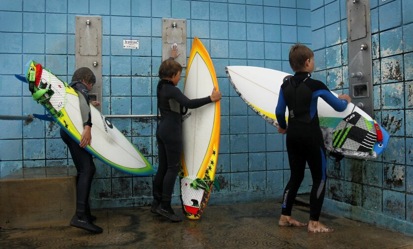 Surf and skate retail sales were up in 2012, according to the Surf Industry Manufacturers Association. In this Dec. 25, 2012 file photo, Jack Gallen, left, and his brother Evan, along with their friend Aidan Becker, right, wash off their brand new surfboards they got for Christmas after surfing at