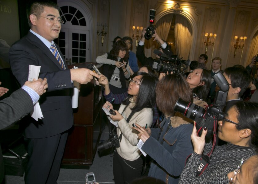 Chinese billionaire Chen Guangbiao, left, , responds to questions at a news conference, in New York, Tuesday, Jan. 7, 2014. Chen announced at the news conference that he underwrite corrective surgery for two women who were burned during a 2001 self-immolation in Tiananmen Square. (AP Photo/Richard Drew)