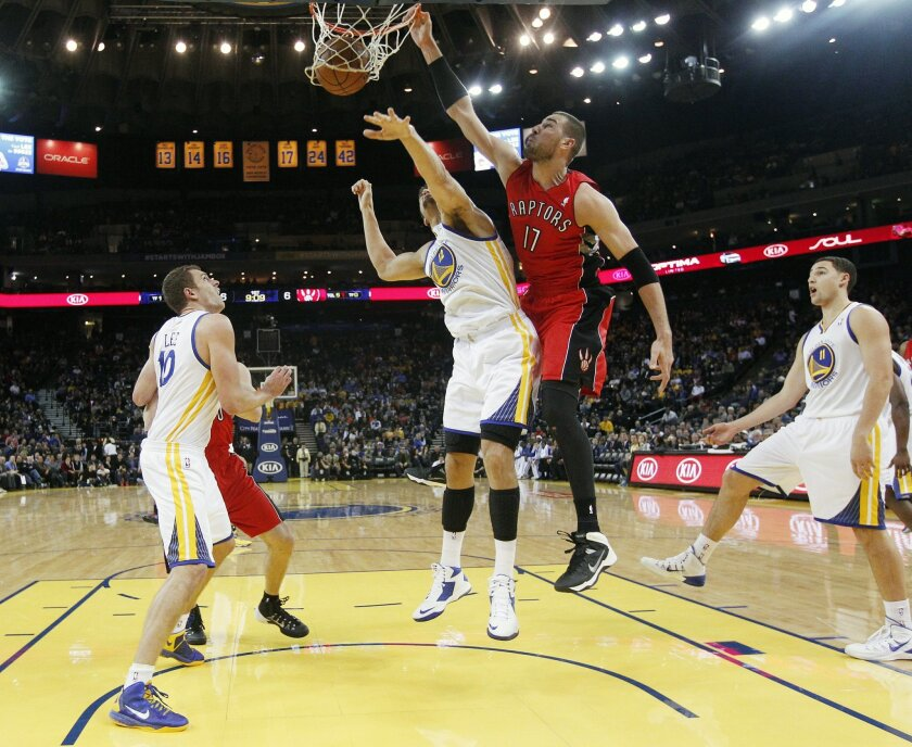 Toronto Raptors' Jonas Valanciunas (17) dunks over Golden State Warriors' Andrew Bogut (12) as Warriors' David Lee (10) and Klay Thompson (11) stand by during the first half of an NBA basketball game on Tuesday, Dec. 3, 2013, in Oakland, Calif. (AP Photo/Marcio Jose Sanchez)