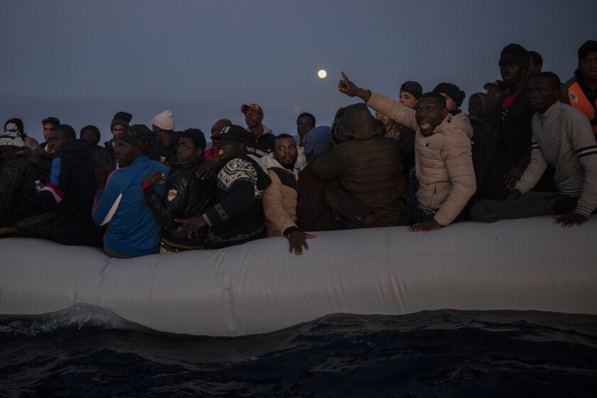 FILE - Migrants and refugees from different African nationalities react on an overcrowded wooden boat, as aid workers of the Spanish NGO Open Arms approach them in the Mediterranean Sea, international waters, off the Libyan coast, in this Friday, Jan. 10, 2020, file photo. When Libyan security forces rescued her earlier this year, a young Somali woman thought it would be the end of her suffering. For more than two years, she had been imprisoned and sexually abused by human traffickers notorious for extorting, torturing and assaulting migrants like her trying to reach Europe. Instead, the 17-year-old said, the sexual assaults against her have continued, only now by guards at the government-run center in the Libyan capital Tripoli where they are being kept. (AP Photo/Santi Palacios, File)