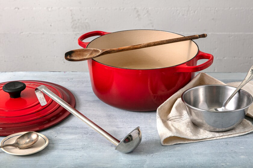 A red Dutch oven, with a wooden spoon across the top, and lid with a ladle, two spoons, a dish towel and a silver bowl.