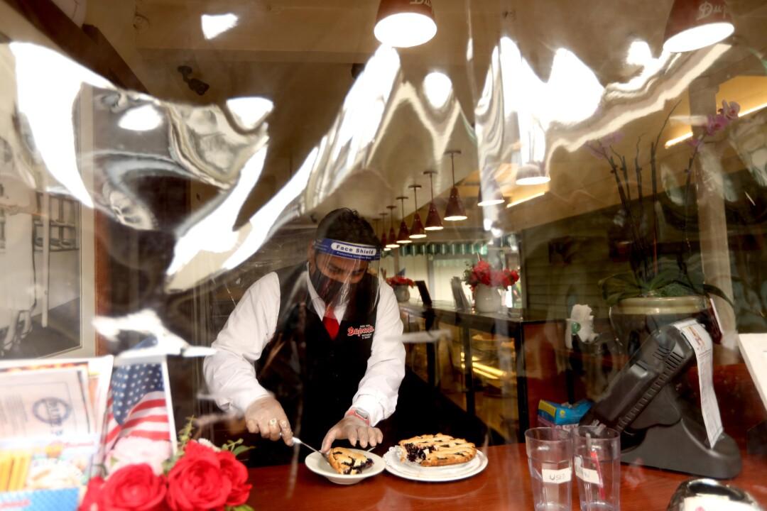 Jose Mlgar cuts a piece of pie for a customer at Du-par's restaurant.