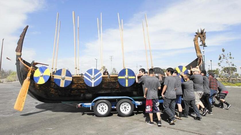 Los estudiantes del taller de carpintería de la escuela preparatoria Marina High mueven un auténtico barco vikingo Valhalla hacia el embarcadero de Sunset Aqcuatic Marina; su construcción en clase les tomó años (Don Leach/Huntington Beach Independent).