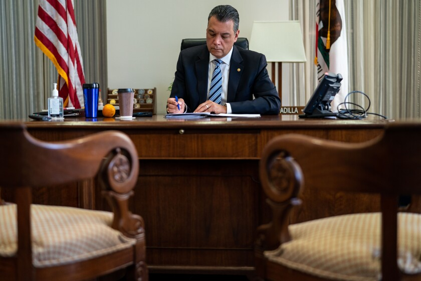 Senator Alex Padilla speaks on a cellphone while standing next to Senator Dianne Feinstein in a Capitol chamber