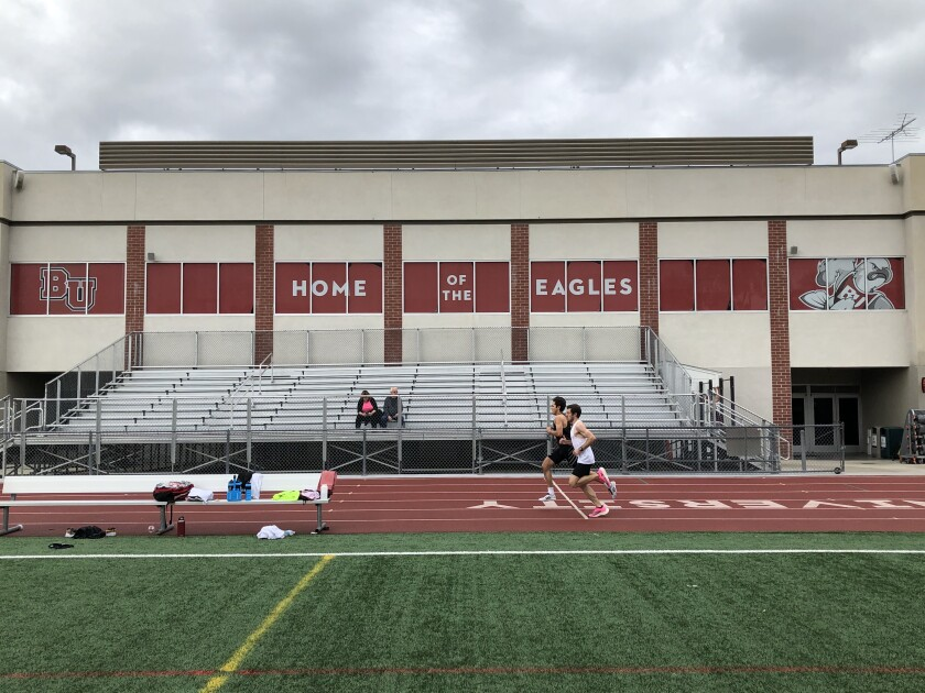 Gabe Plendcio, in black, races assistant coach Ryan Thompson during a time trial in the mile March 14, 2020, at Biola University.
