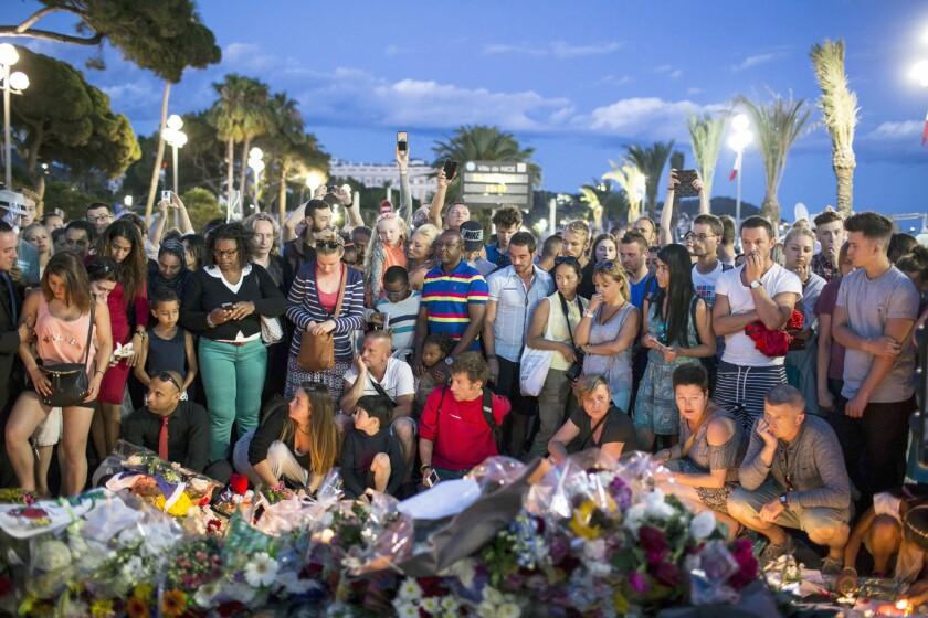 Personas reunidas el viernes 15 de julio de 2016 en un sitio improvisado en memoria de las vÌctimas cerca del sitio donde un camiÛn arrollÛ a decenas de personas en Niza, Francia, el dÌa anterior. (AP Foto/Laurent Cipriani)