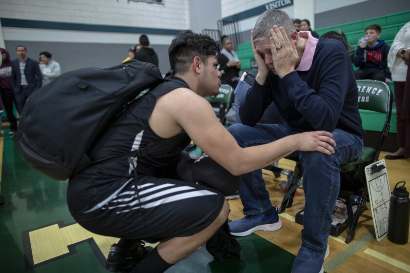 Isaac Torres comforts Roybal High School basketball coach Danny O'Fallon moments after losing 73-33 to Providence in the first round of the state playoffs last season.