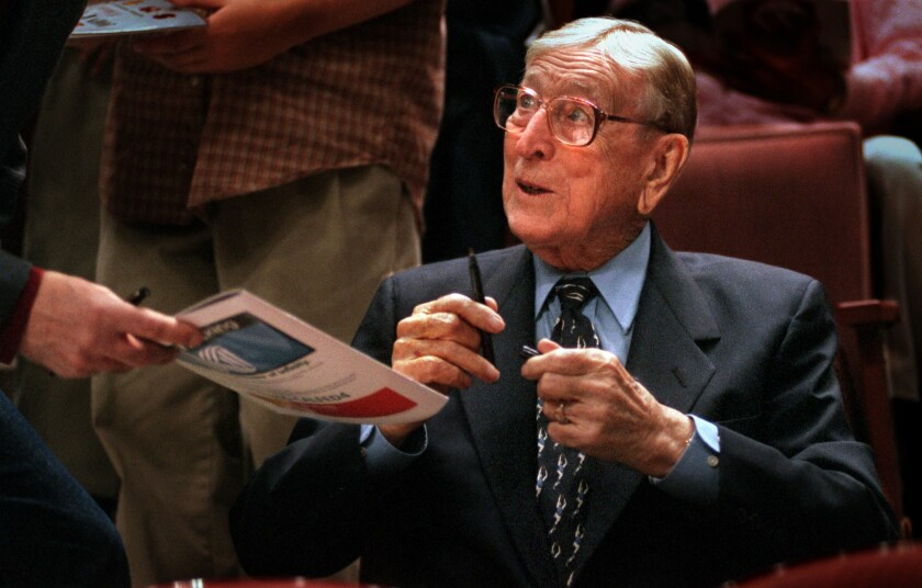 John Wooden signs autographs between games during the Wooden Classic in Anaheim in 1999.