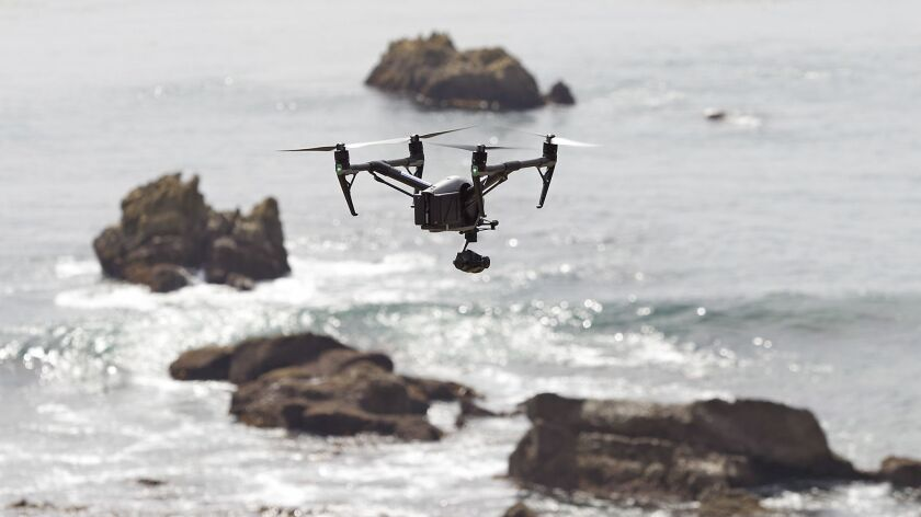 Licensed drone pilot John Barrett flies his professional model camera drone above Rockpile Beach on