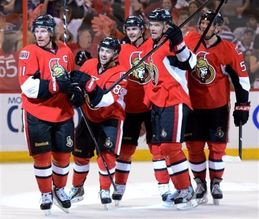 Ottawa Senators' Daniel Alfredsson, Cory Conacher, Erik Karlsson, Milan Michalek and Sergei Gonchar celebrate their team's tying goal against the Montreal Canadiens during the third period of Game 4 of an NHL hockey Stanley Cup playoff series, in Ottawa, Ontario, on Tuesday, May 7, 2013. (AP Photo/The Canadian Press, Sean Kilpatrick)